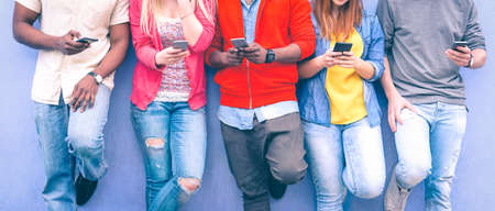 Foto de Teenagers texting mobile phone messages leaning on urban wall - Group of multiracial friends using cellular standing outdoors - Concept of students addiction to social network and telephone technology - Imagen libre de derechos