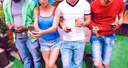 Photo pour Group of friends using mobile phone holding beer standing outdoor at summer  bbq party - Young football fans using smartphone and drinking in bar garden on a spring day - Concept of technology - Image - image libre de droit