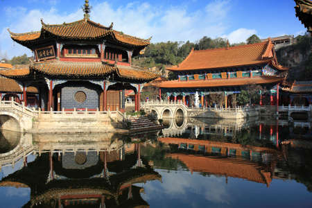 In the courtyard of an old Chinese temple in Kunming, China, with the main worship hall in the background.