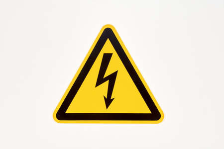 Photo pour Danger sign of high voltage electricity. Yellow triangular label with a zipper in the center on the wall in the store - image libre de droit