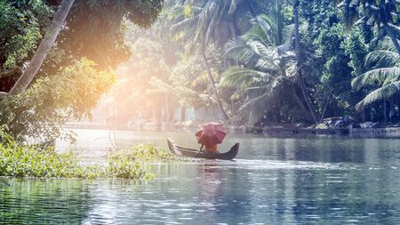 Photo pour A man with an umbrella in a traditional boat sails through the backwaters of Alleppey in Kerala, South India. ALAPPUZHA KERALA - image libre de droit