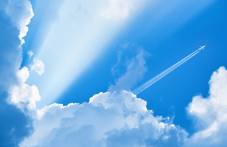 Photo pour Airplane flying in the blue sky among clouds and sunlight - image libre de droit