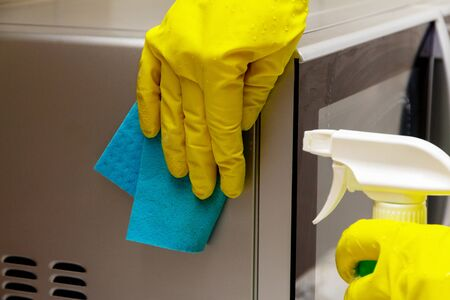 Woman hands in rubber gloves washing microwave from dirt and dust. Kitchen and apartment cleaning