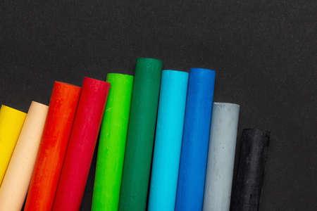 Photo pour Oily wax pastel multicolored crayons on black paper - image libre de droit