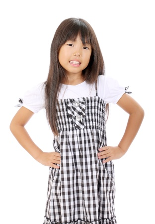 Smiling little girl standing with hands on waistの写真素材