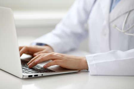 Photo pour Female doctor typing on laptop, close up. - image libre de droit