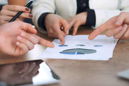 Group of businesspeople or lawyers discussing contract papers and financial figures while sitting at the table. Close-up of human hands at meeting or negotiations. Success and communication concept