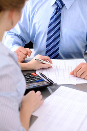 Photo pour Bookkeepers or financial inspector making report, calculating or checking balance. Audit concept - image libre de droit