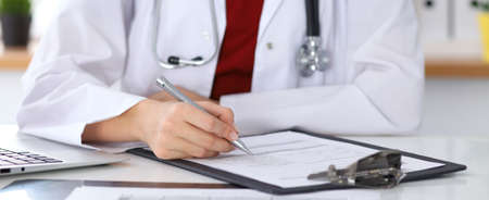 Close up of a female doctor filling up an application form while sitting at the table. Medicine and health care concept