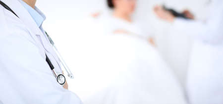 Unknown female doctor with medical staff at hospital. Closeup of stethoscope
