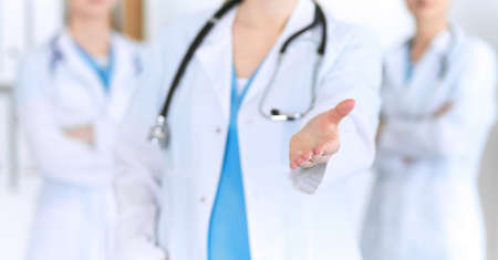 Group of medicine doctors offering helping hand for shaking hand or saving life closeup. Partnership and trust concept in health care or medical cure