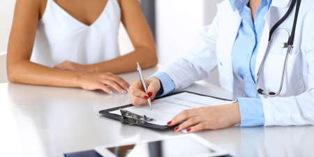 Doctor and happy patient talking while sitting at the desk, close-up of hands. The physician or therapist filling up medical history records. Health care, medicine and patient service concept