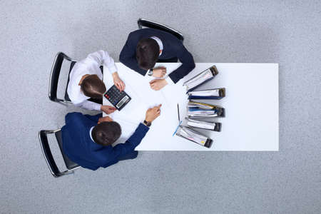 Photo pour Business people at meeting, view from  above. Bookkeeper or financial inspector  making report, calculating or checking balance - image libre de droit