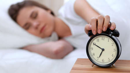 Photo pour Alarm clock opposite of sleepy young woman stretching hand to ringing alarm willing turn it off. Early wake up, not getting enough sleep concept - image libre de droit