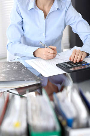 Photo pour Bookkeeper woman or financial inspector  making report, calculating or checking balance, close-up. Business portrait. Copy space area for audit or tax concepts - image libre de droit