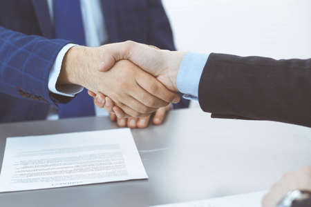 Photo pour Business people shaking hands, finishing up a papers signing. Meeting, agreement and lawyer consulting concept - image libre de droit