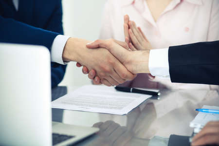 Photo pour Business people shaking hands finishing up a meeting. Handshake at successful negotiation - image libre de droit