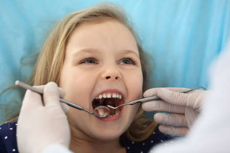 Photo pour Little baby girl sitting at dental chair with open mouth during oral check up while doctor. Visiting dentist office. Medicine concept - image libre de droit