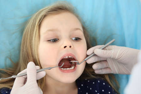 Photo pour Little baby girl sitting at dental chair with open mouth and feeling fear during oral check up while doctor. Visiting dentist office. Medicine concept - image libre de droit