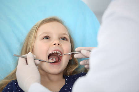 Foto de Little baby girl sitting at dental chair with open mouth during oral check up while doctor. Visiting dentist office. Medicine concept - Imagen libre de derechos