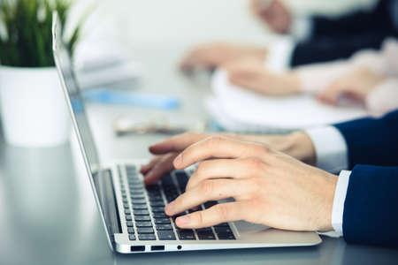Foto de Group of business people working together in office. Man hands typing on laptop computer - Imagen libre de derechos