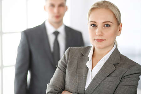Photo pour Business woman standing straight with colleague businessman in office, headshot. Success and corporate partnership concept - image libre de droit