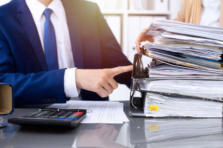 Photo pour Bookkeeper or financial inspector and secretary making report, calculating or checking balance. Internal Revenue Service inspector checking financial document. Audit concept. - image libre de droit