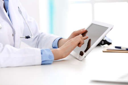 Doctor working table. Woman physician using tablet computer while sitting in hospital office close-up. Healthcare, insurance and medicine concept.