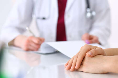 Photo pour Unknown doctor woman consulting patient while filling up an application form at the desk in hospital. Just hands close-up. Medicine and health care concept - image libre de droit
