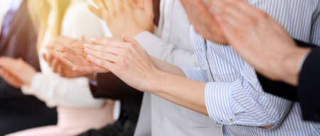 Foto de Business people clapping and applause at meeting or conference, close-up of hands. Group of unknown businessmen and women in modern white office. Success teamwork or corporate coaching concept - Imagen libre de derechos