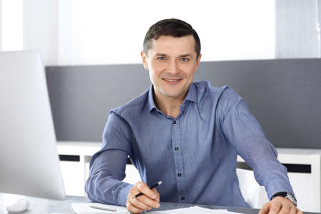 Photo pour Cheerful smiling businessman working with computer in modern office. Headshot of male entrepreneur or director of a company at the workplace. Business concept - image libre de droit