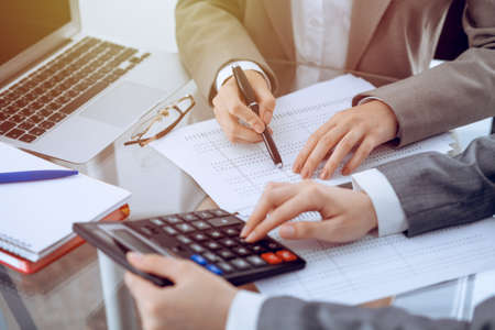 Foto de Two female accountants counting on calculator income for tax form completion hands close-up. Business and audit concept - Imagen libre de derechos