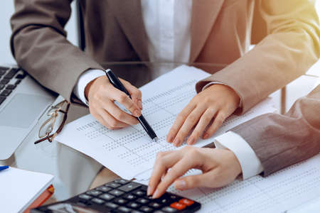 Photo pour Two female accountants counting on calculator income for tax form completion hands close-up. Business and audit concept - image libre de droit