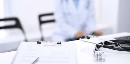 Photo pour Stethoscope, clipboard with medical form lying on hospital reception desk with laptop computer and busy doctor and patient communicating at the background. Medical tools at doctor working table.Medicine concept - image libre de droit