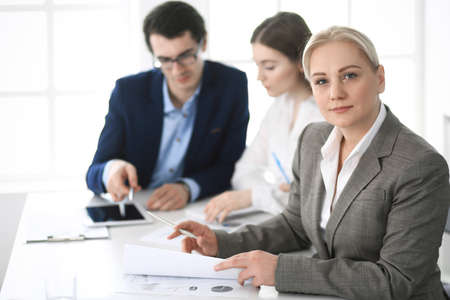 Foto de Headshot of business woman at negotiation. Group of business people discussing questions at meeting in modern office. Teamwork, partnership and business concept - Imagen libre de derechos