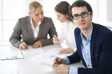 Foto de Group of business people discussing questions at meeting in modern office. Headshot of businessman at negotiation. Teamwork, partnership and business concept - Imagen libre de derechos