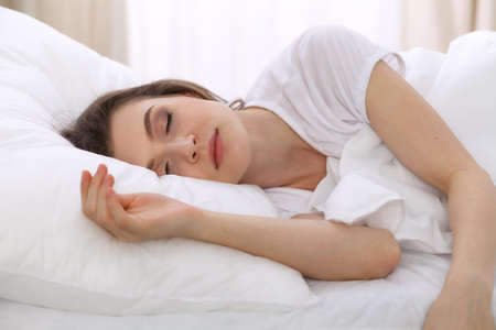 Photo pour Beautiful young woman sleeping while lying in her bed. Concept of pleasant and rest reinstatement for active life - image libre de droit