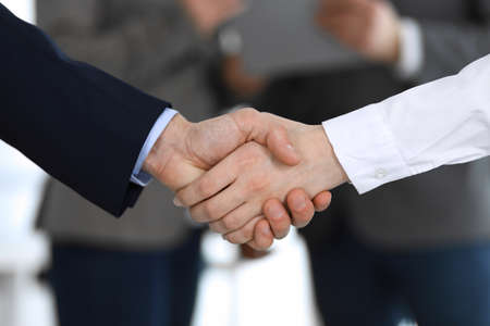 Foto für Business people shaking hands while standing with colleagues after meeting or negotiation, close-up. Group of unknown businessmen and women in modern office. Teamwork, partnership and handshake concept, toned picture - Lizenzfreies Bild