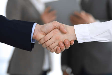 Photo pour Business people shaking hands while standing with colleagues after meeting or negotiation, close-up. Group of unknown businessmen and women in modern office. Teamwork, partnership and handshake concept, toned picture - image libre de droit