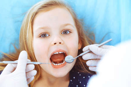 Photo for Little baby girl sitting at dental chair with open mouth during oral check up while doctor. Visiting dentist office. Medicine concept. Toned photo - Royalty Free Image
