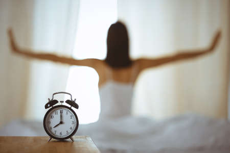 Photo pour Woman stretching hands in bed after wake up, sun flare . Brunette entering a day happy and relaxed after good night sleep and back view. Concept of a new day and joyful weekend - image libre de droit