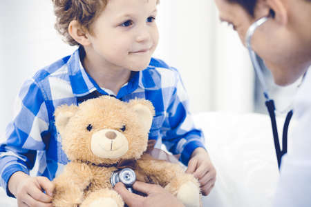 Photo pour Doctor and patient child. Physician examining little boy. Regular medical visit in clinic. Medicine and health care concept - image libre de droit