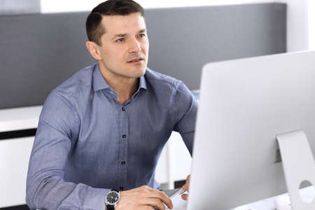 Photo pour Businessman working with computer in modern office. Headshot of male entrepreneur or company director at workplace. Business concept - image libre de droit
