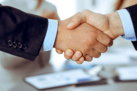 Photo pour Business people shaking hands at meeting while theirs colleagues clapping and applauding. Group of unknown businessmen and women in modern white office. Success teamwork, partnership and handshake concept - image libre de droit