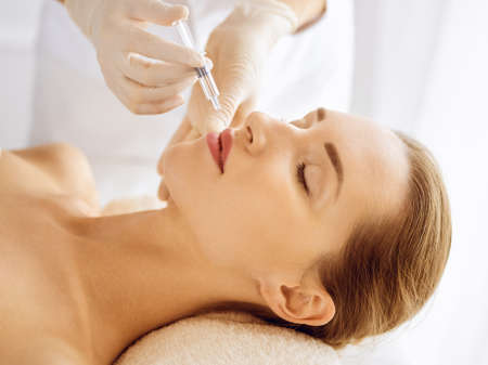 Photo pour Beautiful woman receiving beauty injections with closed eyes. Beautician doctor hands doing beauty procedure to female face with syringe. Cosmetic medicine and surgery concept - image libre de droit