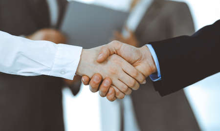 Photo pour Business people shaking hands while standing with colleagues after meeting or negotiation, close-up. Group of unknown businessmen and women in modern office. Teamwork, partnership and handshake concept, toned picture. - image libre de droit