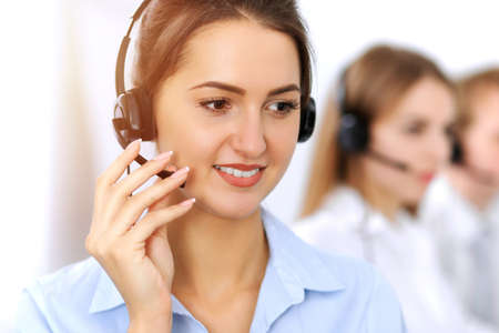 Photo pour Call center. Focus on beautiful business woman using headset in sunny office - image libre de droit