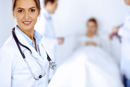Photo pour Female doctor smiling on the background with patient in the bed and two doctors - image libre de droit