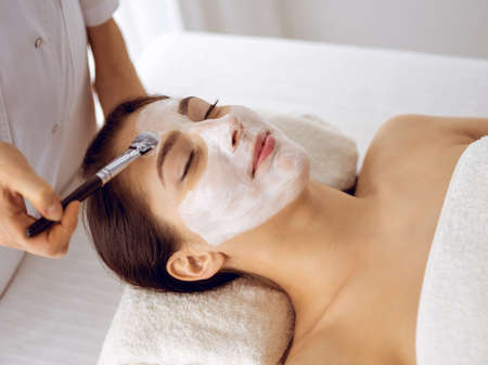 Photo pour Beautiful brunette woman enjoying applying cosmetic mask with closed eyes. Relaxing treatment in medicine and spa center concepts. - image libre de droit