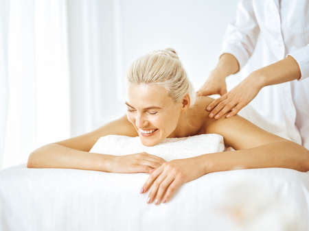 Photo pour Beautiful blonde woman enjoying back massage with closed eyes. Spa salon concept - image libre de droit